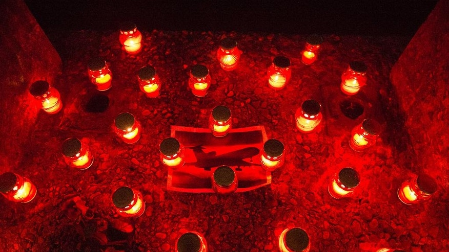 Candles are placed around a photo of the crashed Tu-154 in memory of victims of the crashed plane in the center of Sochi, Russia, Sunday, Dec. 25, 2016.  A Tu-154 operated by the Russian Defense Ministry en route to Syria crashes into the Black Sea minutes after takeoff from Sochi.  Everybody aboard the plane are thought to have perished and the cause of the crash is not immediately known. (AP Photo/Viktor Klyushin)
