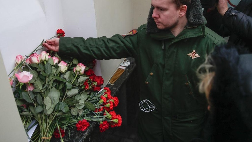 Alexander, a former member of the Alexandrov Ensemble, a well-known military choir lays flowers at the military choir's building in Moscow, Russia, Sunday, Dec. 25, 2016, after a plane carrying 64 members of the Alexandrov Ensemble, crashed into the Black Sea minutes after taking off from the resort city of Sochi. The Russian plane was headed for an air base in Syria with 92 people aboard, Russia's Defense Ministry said. (AP Photo/Pavel Golovkin)