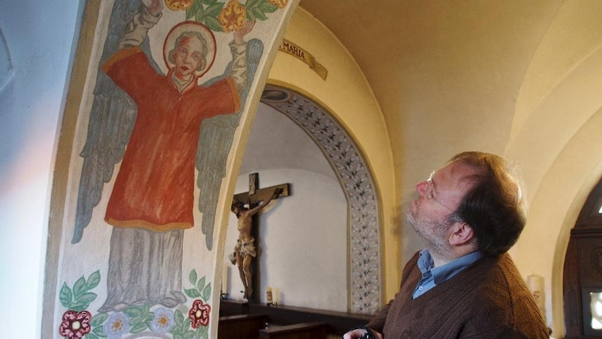 In this Dec. 6, 2016 photo Sister Apollonia historian Volker Schier looks at a mural in the abbey in Altomuenster, Germany. With the closure of the abbey of the uniquely women-led Bridgettine Order the more than 500 books of the library are stored in other locations. (AP Photo/David Rising)