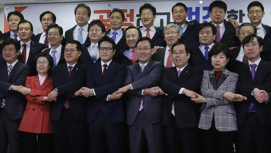 A group of lawmakers of the ruling Saenuri Party joins their hands during a press conference to announce to leave the party at the National Assembly in Seoul, South Korea, Tuesday, Dec. 27, 2016. Dozens of lawmakers split from South Korea's ruling party Tuesday over the corruption scandal involving impeached President Park Geun-hye in a move that could shape presidential elections that might take place in just months. (AP Photo/Ahn Young-joon)