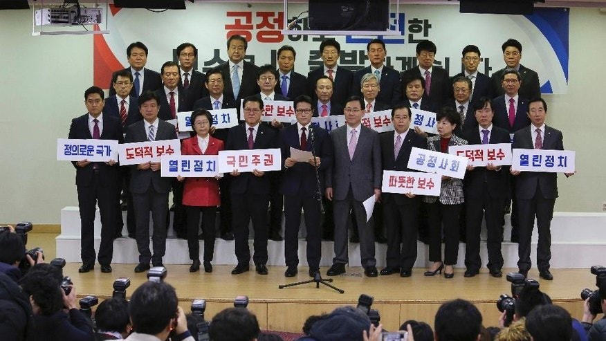 "A group of lawmakers of the ruling Saenuri Party attends a press conference to announce to leave the party at the National Assembly in Seoul, South Korea, Tuesday, Dec. 27, 2016. Dozens of lawmakers split from the party Tuesday over the corruption scandal involving impeached President Park Geun-hye in a move that could shape presidential elections that might take place in just months. The sign in the background reads: ""Open politics and fair society."" (AP Photo/Ahn Young-joon)"