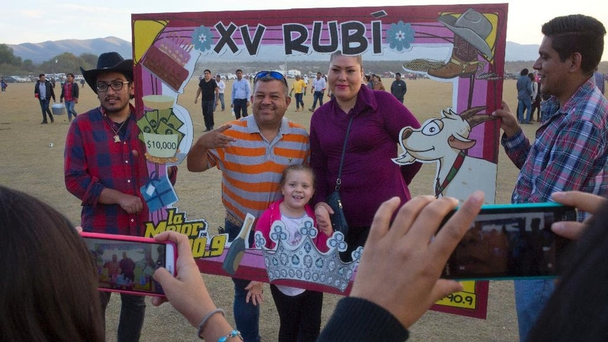 Visitors have their picture taken behind a frame honoring Rubi Ibarra during celebrations for her down-home 15th birthday near the village of Laguna Seca, San Luis Potosi State, Mexico, Monday Dec. 26, 2016. Rubi's 15th birthday party resembled a rock concert on Monday after thousands of people showed up in response to an invitation by her father that went viral and made her the toast of the country. (AP Photo/Enric Marti)