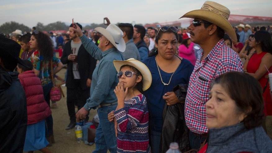 A family attends a party honoring Rubi Ibarra during celebrations for her down-home 15th birthday near the village of Laguna Seca, San Luis Potosi State, Mexico, Monday Dec. 26, 2016. Rubi's 15th birthday party resembled a rock concert on Monday after thousands of people showed up in response to an invitation by her father that went viral and made her the toast of the country. (AP Photo/Enric Marti)