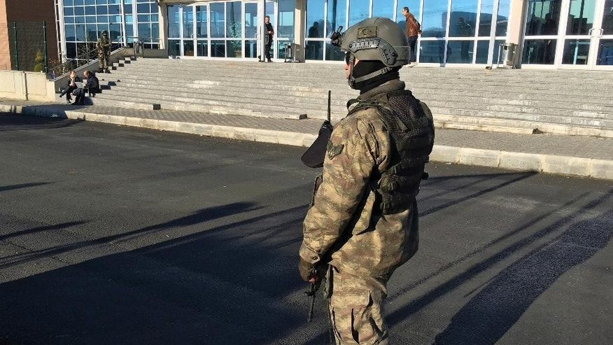 A paramilitary police officer stands at the entrance of Silivri Prison and Courthouse complex where 29 Turkish former police officers are on trial in the outskirts of Istanbul, Tuesday, Dec. 27, 2016. They are accused of aiding the failed military coup in July — the first trial over the attempt that led to some 270 deaths.(AP Photo/Mehmet Guzel)