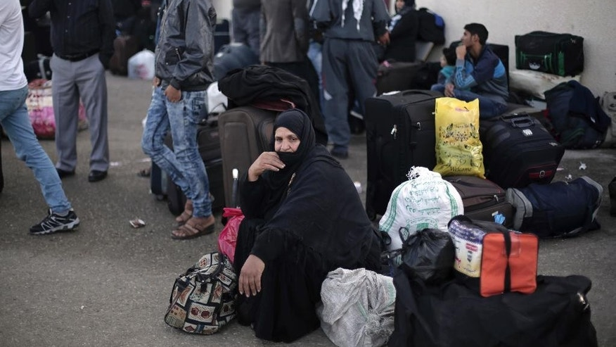 In this Nov. 14, 2016 photo, a Palestinian woman sits next to her luggage as she waits to cross to the Egyptian side of the Rafah border crossing, in the Gaza Strip. For most of the past decade, Egypt has been a quiet partner with Israel in a blockade on the Hamas-ruled Gaza Strip that has stifled the economy and largely blocked its 2 million people from moving in and out of the territory. But after a three-year crackdown, there are signs that Egypt is easing the pressure in a step to repair its shattered ties with the Islamic militant group. (AP Photo/Khalil Hamra)