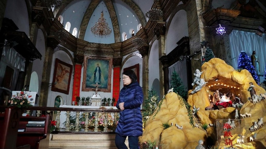 "A woman walks past a decoration displaying a baby Jesus doll part of a Nativity scene at the Nantang Catholic Church in Beijing, Wednesday, Dec. 28, 2016. China's head of religious affairs said that Beijing is willing to have constructive dialogue with the Vatican but stressed that Catholics should ""hold up high the flag of patriotism"" and adapt Catholicism to Chinese society. (AP Photo/Andy Wong)"