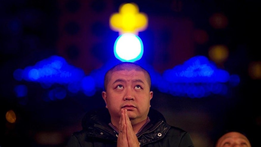 In this photo taken Wednesday, Dec. 24, 2014, a man prays during mass on the eve of Christmas at the South Cathedral official Catholic church in Beijing. China says Tuesday, Dec 27, 2016, it is willing to have constructive dialogue with the Vatican but stresses the importance of patriotism to Beijing and adapting Catholicism to Chinese society. (AP Photo/Ng Han Guan)