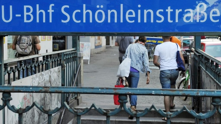 FILE - In this July 19, 2010 file picture people leave the subway station Schoenleinstrasse in Berlin. German police are questioning seven young men Tuesday Dec. 27, 2016  who are suspected of trying to set a homeless man alight in a Berlin subway station over Christmas.  (Tobias Kleinschmidt/dpa via AP,file)