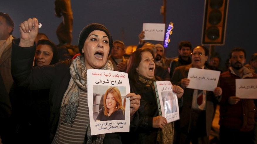 Protesters chant slogans demanding the release of kidnapped journalist Afrah Shawqi al-Qaisi, seen in posters, during a demonstration, in Baghdad, Iraq, Tuesday, Dec. 27, 2016. Late Monday night unidentified gunmen broke into the house of al-Qaisi, a journalist and activist in Baghdad and kidnapped her, Iraq's Interior Ministry said on Tuesday, a reminder of the dangers journalists face in a country where authorities have struggled to maintain security nationwide. (AP Photo/ Karim Kadim)