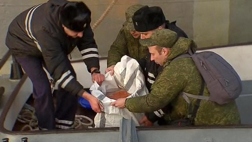 In this Tuesday, Dec. 27, 2016 frame grab made available by Russian Rossiya One TV Channel Emergency Ministry soldiers pack a flight recorder of the crashed plane, on a pier just outside Sochi, Russia. (Rossiya One TV Channel photo via AP)  MANDATORY CREDIT