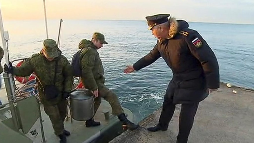 In this Tuesday, Dec. 27, 2016 frame grab made available by Russian Rossiya One TV Channel Emergency Ministry soldiers carry a container with flight recorder of the crashed plane, on a pier just outside Sochi, Russia. (Rossiya One TV Channel photo via AP)  MANDATORY CREDIT