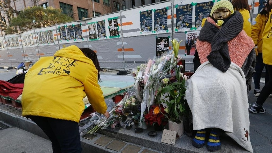 A college student places flowers next to the statue of a girl representing victims of Japanese sexual slavery in front of the Japanese Embassy in Seoul, South Korea, Wednesday, Dec. 28, 2016. South Korea's opposition politicians on Wednesday called for nullifying a settlement reached between Seoul and Tokyo on compensation for South Korean women forced into sexual slavery by Japan's military in World War II. (AP Photo/Ahn Young-joon)