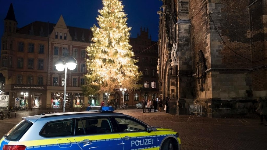 In this Dec. 24, 2016 picture a police car stands near the Market Church in Hannover, Germany, as security was tightened on Christmas Eve in many German cities after the Dec.19 Christmas market attack in Berlin. (Peter Steffen/dpa via AP)