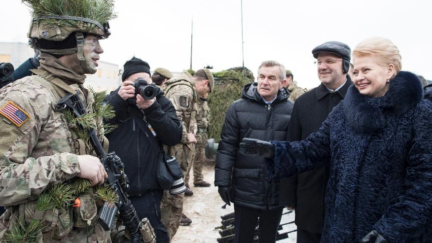 FILE - In this Friday, Dec. 2, 2016 file photo, Lithuanian President Dalia Grybauskaite, right, speaks with a soldier from the US Army, left, during the NATO military exercise 'Iron Sword 2016' at a training range in Pabrade, north of the capital Vilnius, Lithuania. Europe used to be good at influencing people and nations without toting a gun. It was called soft power, and depended on aid, trade, diplomacy, even culture. If there is one lesson for 2017, it is that soft power alone won't work anymore. (AP Photo/Mindaugas Kulbis, File)