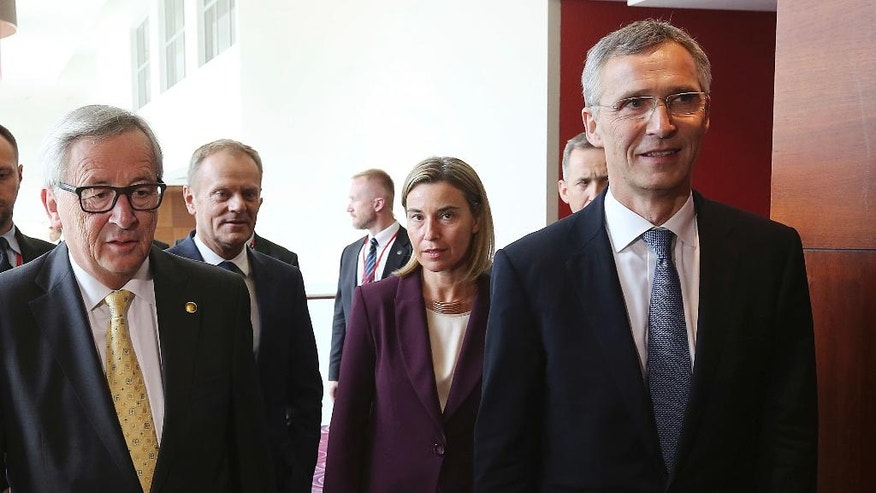FILE - In this Friday, July 8, 2016 file photo, President of European Commission Jean-Claude Juncker, left, President of the European Council Donald Tusk, second left, EU foreign policy chief Federica Mogherini, second right, and NATO Secretary General Jens Stoltenberg, right, arrive for a EU Signing Ceremony of the EU-NATO Joint Declaration during the NATO summit in Warsaw, Poland. Europe used to be good at influencing people and nations without toting a gun. It was called soft power, and depended on aid, trade, diplomacy, even culture. If there is one lesson for 2017, it is that soft power alone won't work anymore. (AP Photo/Czarek Sokolowski, File)