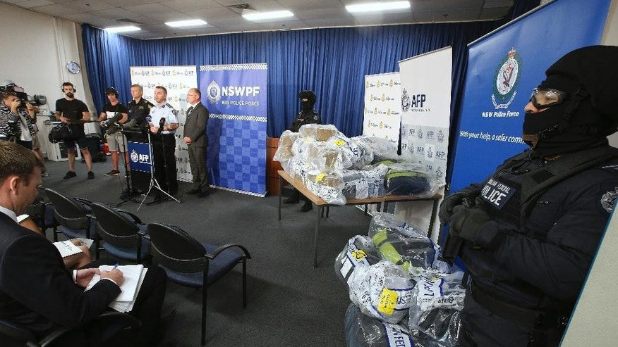 Armed police officers, right, guard a haul of drugs that are on display at an Australian Federal Police office as officials brief the media in Sydney, Australia, Thursday, Dec. 29, 2016. Officials have seized more than a ton of cocaine worth about 360 million Australian dollars ($260 million) in what police have dubbed one of the largest drug busts in the nation's history. (AP Photo/Rick Rycroft)