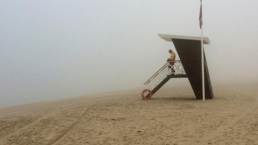 A lifeguard looks out at the fog covered empty Umm Suqeim beach, in Dubai, United Arab Emirates, Wednesday, Dec. 28, 2016. A heavy seasonal fog engulfed the skyscraper-lined skyline of Dubai for several hours, causing some flights to be delayed at the world's busiest international airport. (AP Photo/Kamran Jebreili)