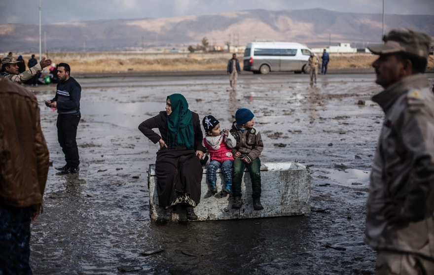 A Iraqi woman displaced from Mosul and her 2 children sit on top of an old refrigerator at a gathering point for displaced people, in Bartella, around 30 km (19 miles), from Mosul, Iraq, Monday, Dec. 26, 2016. (AP Photo/Manu Brabo)