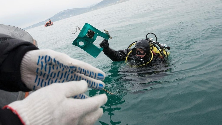A Russian Emergency Ministry diver lifts a fragment of a plane in the Black Sea, outside Sochi, Russia, Tuesday, Dec. 27, 2016. Investigators have recovered the flight-data recorder from a crashed Russian military plane. Teams are beginning to review the data to learn why the jet went down shortly after taking off Sunday from the city of Sochi. The crash killed all 92 people aboard the Tu-154, including members of a famous choir. (AP Photo/Viktor Klyushin)