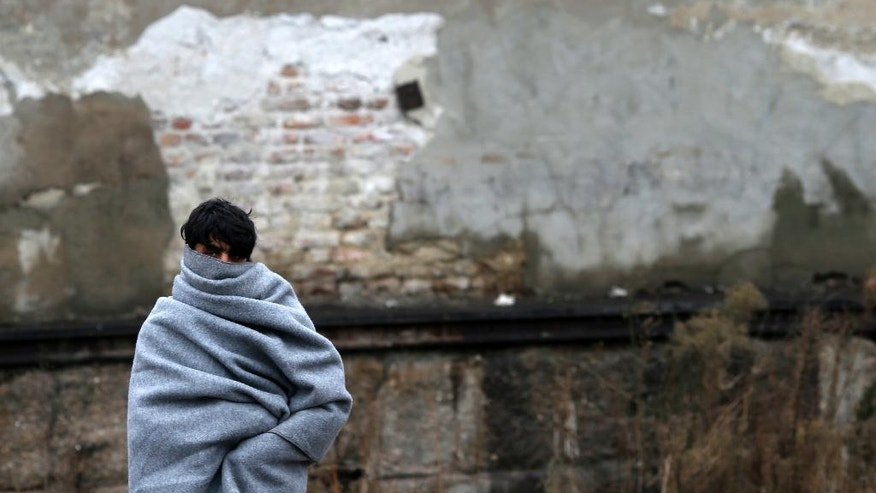 A migrant wrapped in a blanket walks in front of an abandoned warehouse, in Belgrade, Serbia, Tuesday, Dec. 20, 2016. Minors make up about 40 percent of the thousands of migrants stranded in Serbia seeking ways to cross the heavily guarded borders of neighboring European Union nations Croatia or Hungary, according to the United Nations Children's Fund. Some of the minors are separated from their families either by chance or by smugglers. (AP Photo/Darko Vojinovic)
