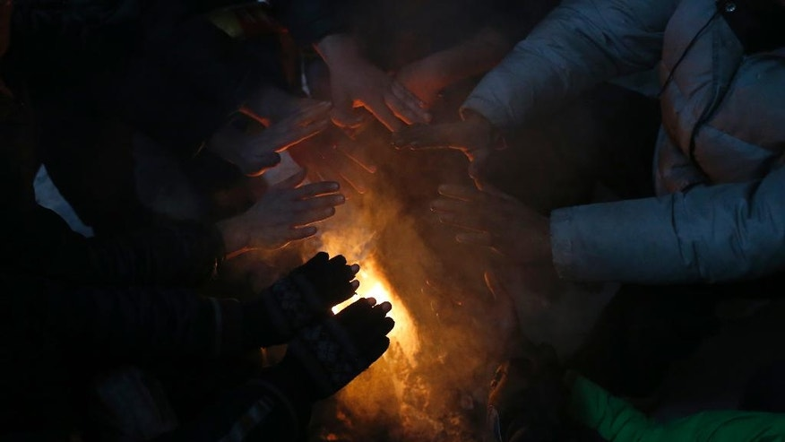 Migrants warm themselves by the fire in an abandoned warehouse, in Belgrade, Serbia, Tuesday, Dec. 20, 2016. Minors make up about 40 percent of the thousands of migrants stranded in Serbia seeking ways to cross the heavily guarded borders of neighboring European Union nations Croatia or Hungary, according to the United Nations Children's Fund. Some of the minors are separated from their families either by chance or by smugglers. (AP Photo/Darko Vojinovic)