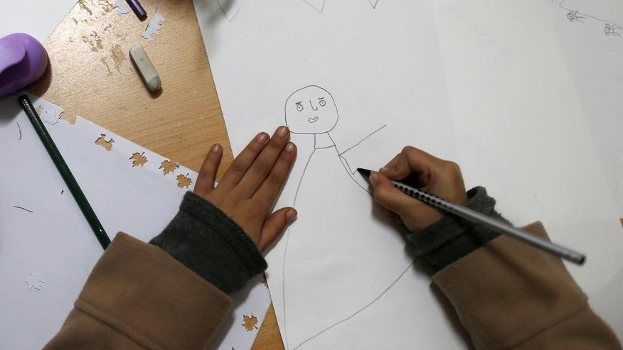 A migrant girl draws a picture during her stay in the Miksaliste hub for refugees and migrants, in Belgrade, Serbia, Wednesday, Dec. 21, 2016. Minors make up about 40 percent of the thousands of migrants stranded in Serbia seeking ways to cross the heavily guarded borders of neighboring European Union nations Croatia or Hungary, according to the United Nations Children's Fund. Some of the minors are separated from their families either by chance or by smugglers. (AP Photo/Darko Vojinovic)