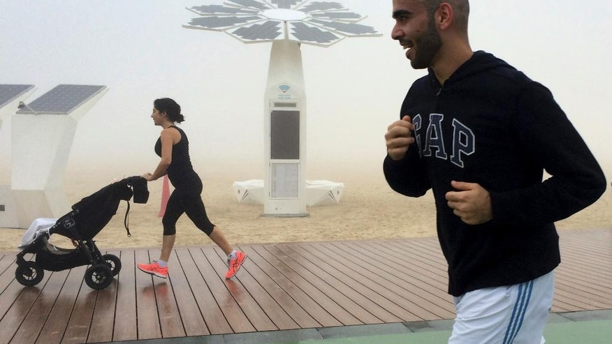 People jog at the Umm Suqeim beach on a foggy morning in Dubai, United Arab Emirates, Wednesday, Dec. 28, 2016. A heavy seasonal fog engulfed the skyscraper-lined skyline of Dubai for several hours, causing some flights to be delayed at the world's busiest international airport. (AP Photo/Kamran Jebreili)