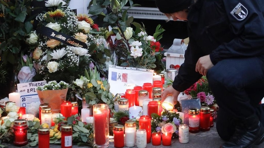 FILE - In this Dec. 20, 2016 file photo a police officer lights a candle in Berlin, Germany the day after a truck ran into a crowded Christmas market nearby. German prosecutors say they've detained a Tunisian man they think may have been involved in last week's truck attack on a Christmas market in Berlin. Federal prosecutors said Wednesday Dec. 28, 2016  the 40-year-old was detained during a search of his home and business.   (AP Photo/Matthias Schrader,file)