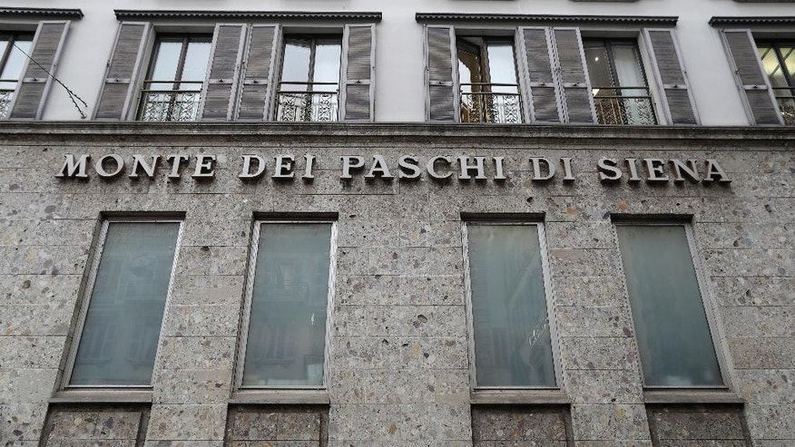 FILE - In this file photo dated Monday, Dec. 19, 2016, the facade of a branch of the ' Monte Dei Paschi di Siena ' bank in Milan, Italy.  In a statement issued late Monday Dec. 27, 2016, the European Central Bank estimates the Monte Dei Paschi di Siena bank will need more rescue money than previously expected. (AP Photo/Antonio Calanni, FILE)