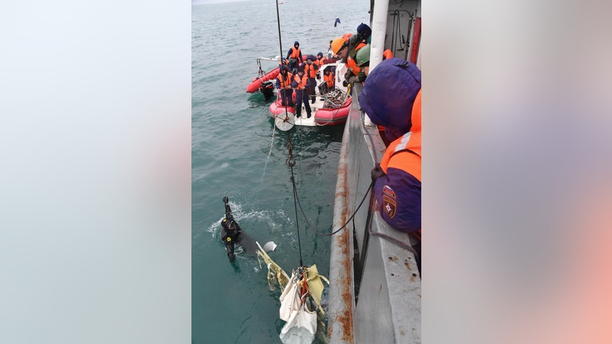 In this photo taken on Wednesday, Dec. 28, 2016 photo provided by the Russian Emergency Ministry Press Service, ministry employees lift a fragment of a plane in the Black Sea, outside Sochi, Russia. Russia's Defense Ministry says search teams have recovered another flight recorder from a military plane that crashed in the Black Sea, killing all 92 aboard. (Vladimir Velengurin/Emergency Situations Ministry Photo via AP)