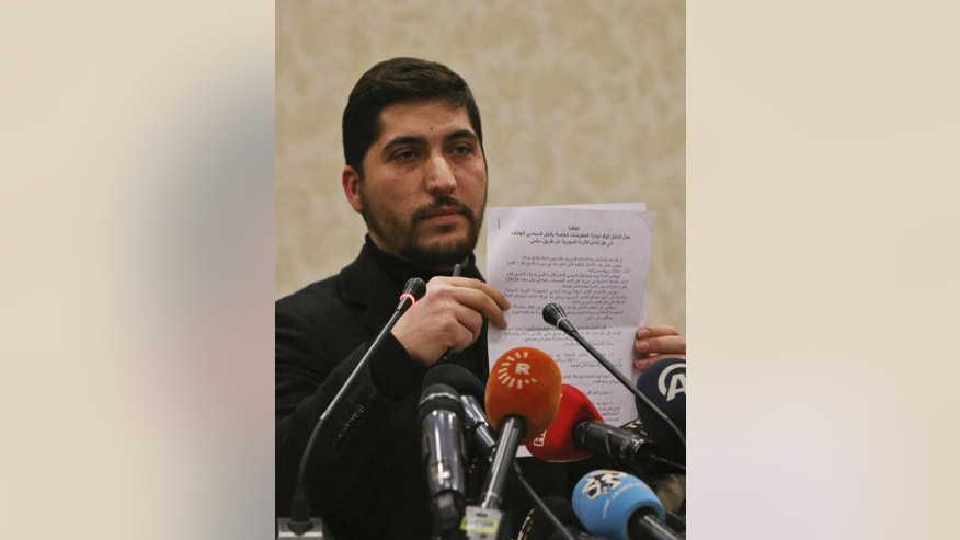 Osama Abu Zeid of the the main moderate Syrian opposition group Free Syrian Army, shows what he said is a copy of the five-point cease-fire agreement for Syria, during a news conference in Ankara, Turkey, Thursday, Dec. 29, 2016. Abu Zeid said that his group, one of the 13 armed opposition factions, had agreed to abide by the nationwide cease-fire agreement that will go into effect at midnight Thursday. The truce will be followed by peace talks in Kazakhstan that will focus on finding a solution for Syria's crisis, Abu Zeid said. (AP Photo/Burhan Ozbilici)