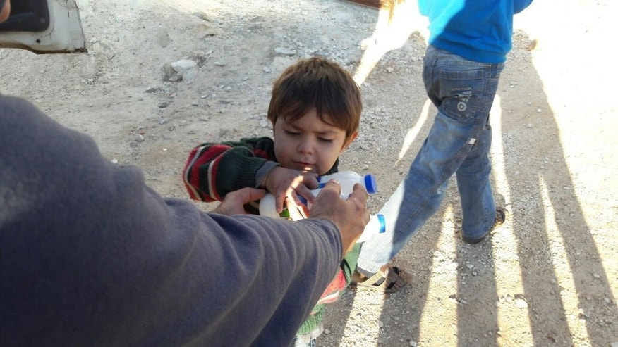 A Syrian child receiving food.