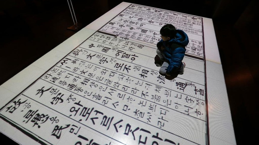 "In this Wednesday, Dec. 28 photo, a boy sits on a screen showing Korean traditional characters at the National Hangeul Museum in Seoul, South Korea. Impeached President Park Geun-hye's surname is ""Park,"" right? Nope. In Korean it's closer to ""Bahk."" Park's allegedly corrupt confidante, Choi Soon-sil, pronounces her name more like ""Chwey"" than the way it's rendered in English. There is a gulf, often a wide one, between the way Koreans write their names in English and the way they actually sound. (AP Photo/Ahn Young-joon)"