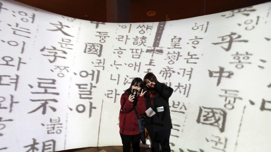 "In this Wednesday, Dec. 28 photo, high school students take a selfie in front of a screen showing Korean traditional characters at the National Hangeul Museum in Seoul, South Korea. Impeached President Park Geun-hye's surname is ""Park,"" right? Nope. In Korean it's closer to ""Bahk."" Park's allegedly corrupt confidante, Choi Soon-sil, pronounces her name more like ""Chwey"" than the way it's rendered in English. There is a gulf, often a wide one, between the way Koreans write their names in English and the way they actually sound. (AP Photo/Ahn Young-joon)"