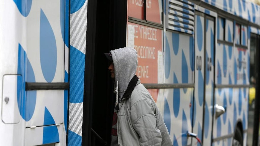 In this photo taken on Wednesday, Dec. 21, 2016, a homeless person asks for information a social worker at the shower bus run by the Greek Praksis Non Governmental Organization at Koumoundourou square in central Athens. Poverty rates have surged here since the start of the crisis in late 2009, with nearly 36 percent of the country living in financial distress, according to European Unions statistics agency, Eurostat. (AP Photo/Thanassis Stavrakis)