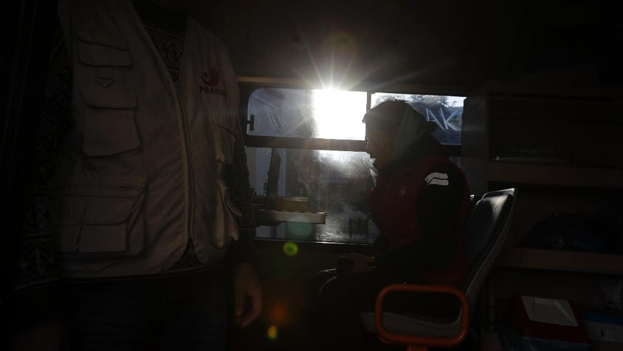 In this photo taken on Monday, Dec. 19, 2016, a homeless person talks with a social worker on a shower bus run by the Greek Praksis, Non Governmental Organization, at Koumoundourou square in central Athens. Poverty rates have surged here since the start of the crisis in late 2009, with nearly 36 percent of the country living in financial distress, according to European Unions statistics agency, Eurostat. (AP Photo/Thanassis Stavrakis)