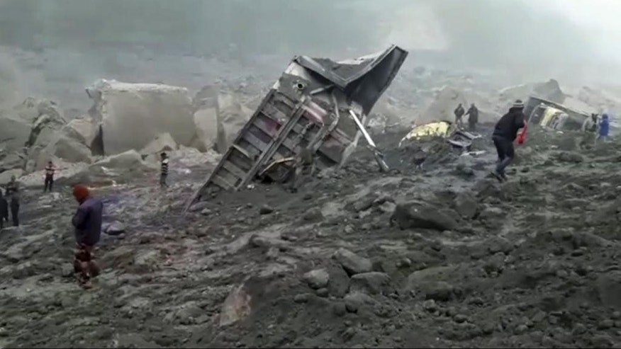 In this photo made from video, people watch an excavator dig into a collapsed mine, Friday, Dec. 30, 2016, in the Godda district, in eastern India. The coal mine collapsed late Thursday and could have over a dozen miners trapped inside. (AP Photo)