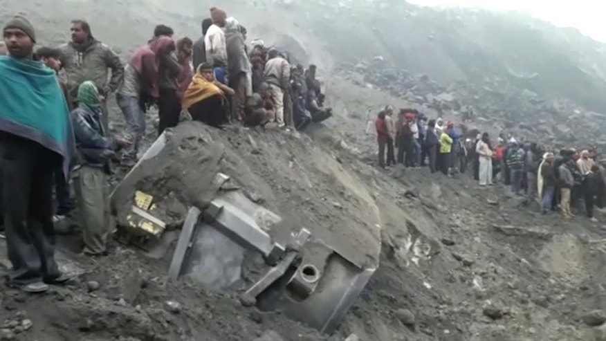 In this photo made from video, people watch survey the damage of a collapsed mine, Friday, Dec. 30, 2016, in the Godda district, in eastern India. The coal mine collapsed late Thursday and could have over a dozen miners trapped inside. (AP Photo)