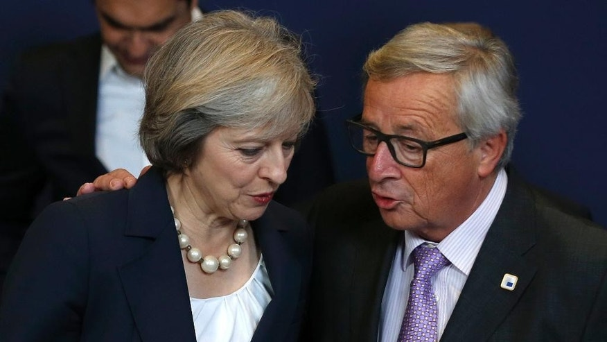 FILE - This is a Thursday, Oct. 20, 2016 file photo of British Prime Minister Theresa May, left, and European Commission President Jean Claude Juncker as they talk during an EU summit group photo in Brussels . Europe's leaders are not expecting a smooth ride in 2017 following a year marked by political upheaval, terror attacks, unchecked immigration, and a rising military threat from Russia.  Britain is suing for divorce, the far-right is on the march, some former Soviet satellites are backsliding even as Russia seeks to expand its influence.  (AP Photo/Alastair Grant, File)