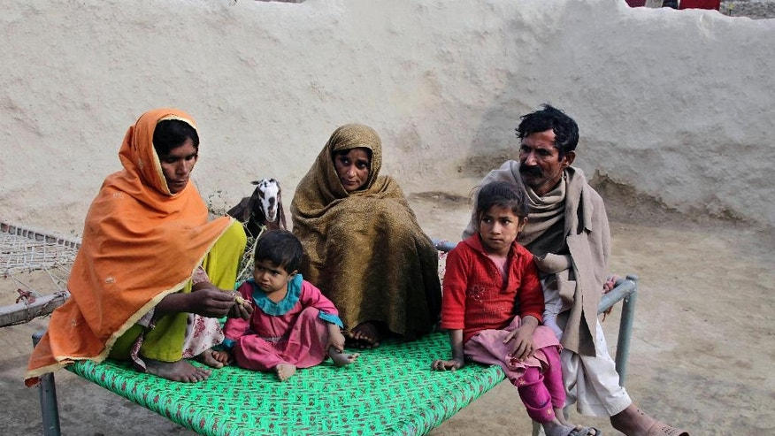 In this Wednesday, Dec. 21, 2016 photo, Wazir Ahmed, right, who married his underage daughter to a 36 year-old man, sits with his wives in Jampur, Pakistan. The marriage was in exchange for a second wife who is the man's sister. He hopes she will give him a son. He says he feels no remorse because tradition and faith demands parents marry their daughters, who he calls burdens, soon after they reach puberty. (AP Photo/K.M. Chaudhry)