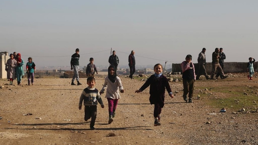 Displaced children running behind a humanitarian aid truck in Mosul, Iraq, Friday, Dec. 30, 2016. Iraq's special forces are continuing to push back Islamic State militants in the eastern sector of Mosul. (AP Photo/ Khalid Mohammed)