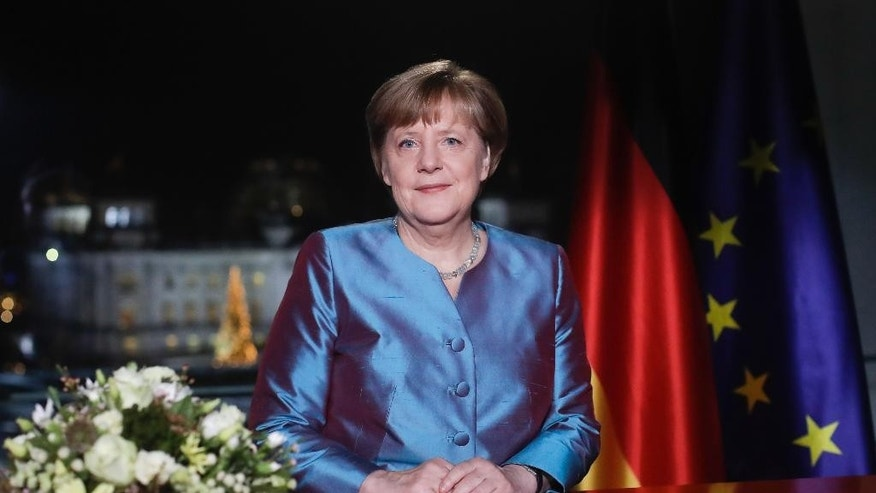 German Chancellor Angela Merkel poses for photographs after the television recording of her annual New Year's speech at the chancellery in Berlin, Friday, Dec. 30, 2016, (AP Photo/Markus Schreiber, Pool)