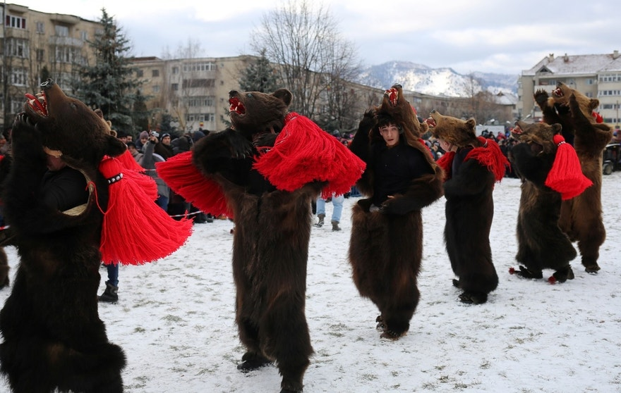 Dancers wearing costumes made of bearskins dance in the town of Comanesti, Romania December 30, 2016. People from this region follow a pre-Christian rural tradition where they sing and dance to ward off evil.  REUTERS/Stoyan Nenov - RTX2WY3Q