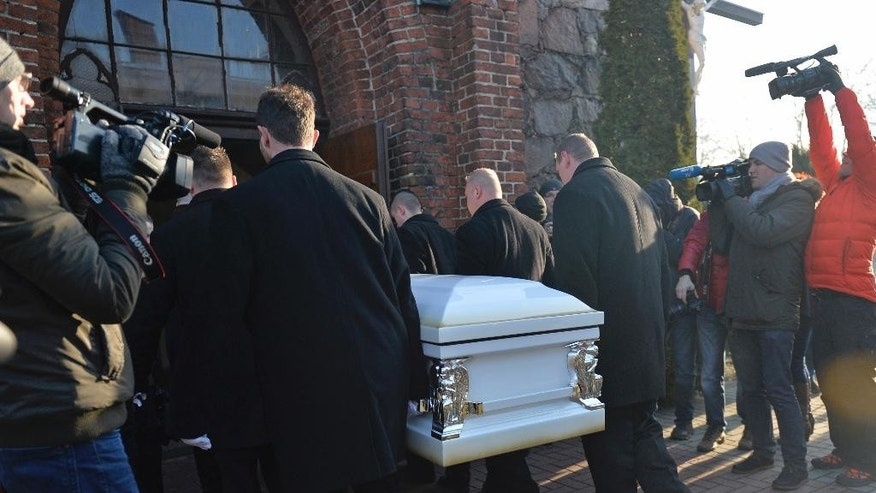 The coffin with the body of Lukasz Urban, the Polish truck driver killed in the Berlin Christmas market attack, is carried into the church in Banie, Poland, Friday, Dec. 30, 2016, ahead of the funeral ceremonies. (AP Photo/Lukasz Szelemej)