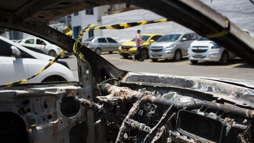 A burned car sits in the parking lot of the police station in Belford Roxo, Brazil, Friday, Dec. 30, 2016. This burned vehicle, matching the description of the car rented by Greece's ambassador to Brazil Kyriakos Amiridis, was found with a body inside it in Nova Iguacu, but forensics experts have not yet identified the dead person. Amiridis went missing on Monday in the city of Nova Iguacu. (AP Photo/Leo Correa)