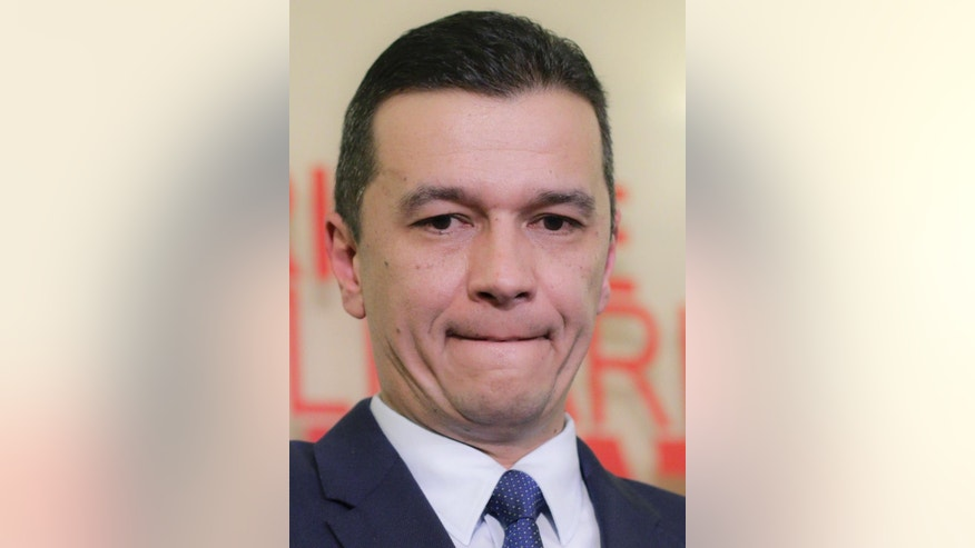 In this Dec. 28, 2016, picture, Sorin Grindeanu, Romania's Prime Minister designate grimaces during a press conference in Bucharest, Romania. Romania's president nominated regional politician, Sorin Grindeanu, 43, as the next prime minister, after turning down economist Sevil Shhaideh, who could have become the country's first female Muslim premier.(AP Photo/Octav Ganea)