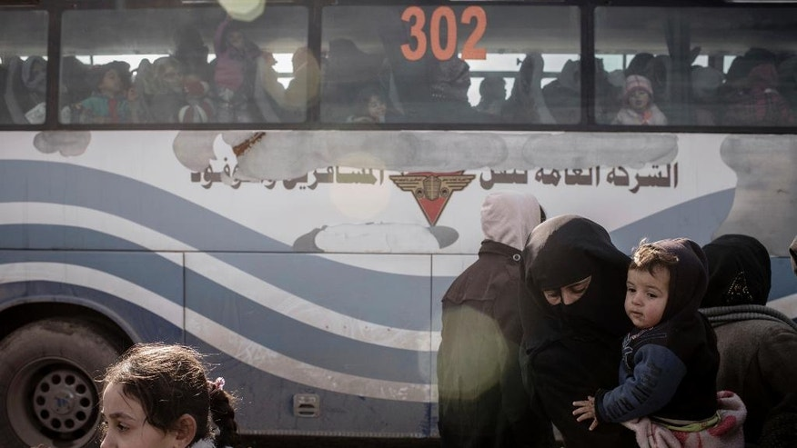 Iraqis displaced from Mosul load onto buses for transportation to IDP camps, in near Bartella, Iraq on Thursday, Dec. 29, 2016. Breaking a two-week lull in fighting, Iraqi troops backed by the U.S.-led coalition's airstrikes and artillery pushed deeper into eastern Mosul on Thursday in a multi-pronged assault against Islamic State militants in the city. (AP Photo/Cengiz Yar)