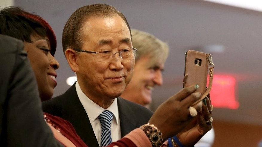 United Nations Secretary-General Ban Ki-moon, poses for a selfie photo with one of his staff members on his last day at the U.N. headquarters on Friday, Dec. 30, 2016. (AP Photo/Mary Altaffer)