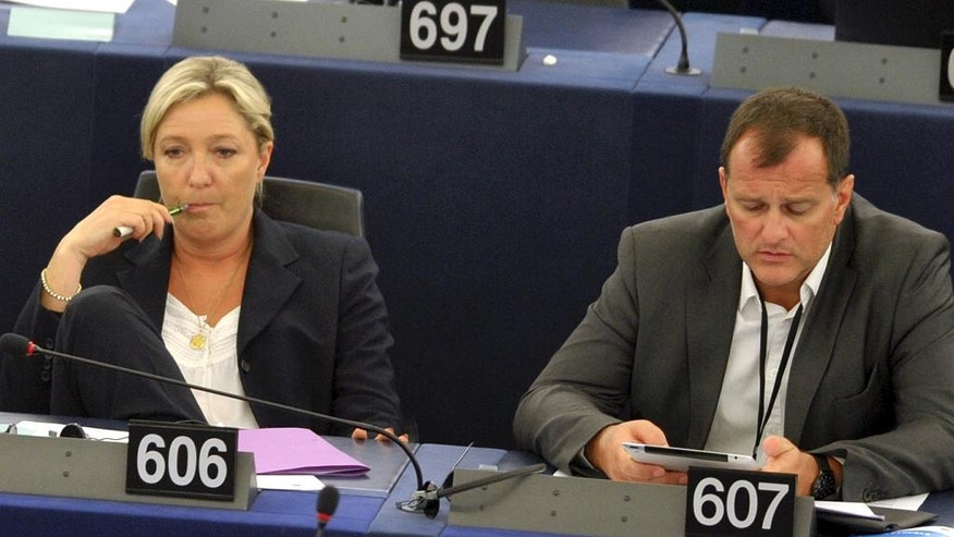 "FILE - In this July 15, 2014 file photo, French far right leader Marine Le Pen, left, and party vice-president Louis Aliot listen to debates at the European Parliament in Strasbourg, eastern France. Money, and how to get it, has dogged French far-right presidential contender Marine Le Pen for years. Now, as her National Front party's treasurer says it's looking ""everywhere"" for the 20 million euros ($21 million) needed to fund upcoming campaigns, she may be looking to Russia for cash  again. . (AP Photo/Christian Lutz, File)"