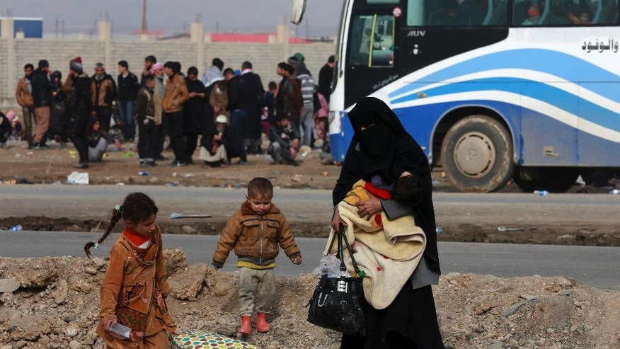 Displaced Iraqis, who fled fighting between Iraqi security forces and Islamic State militants, waiting at the gathering point to be taken for a camp for internally displaced people, in Bartella, around 19 miles (kilometers), from Mosul, Iraq, Saturday, Dec 31, 2016. (AP Photo/ Khalid Mohammed)